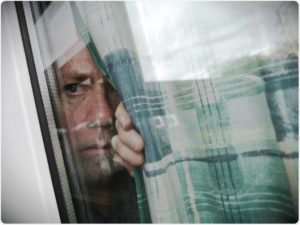 человек со страхом смотрит в окно